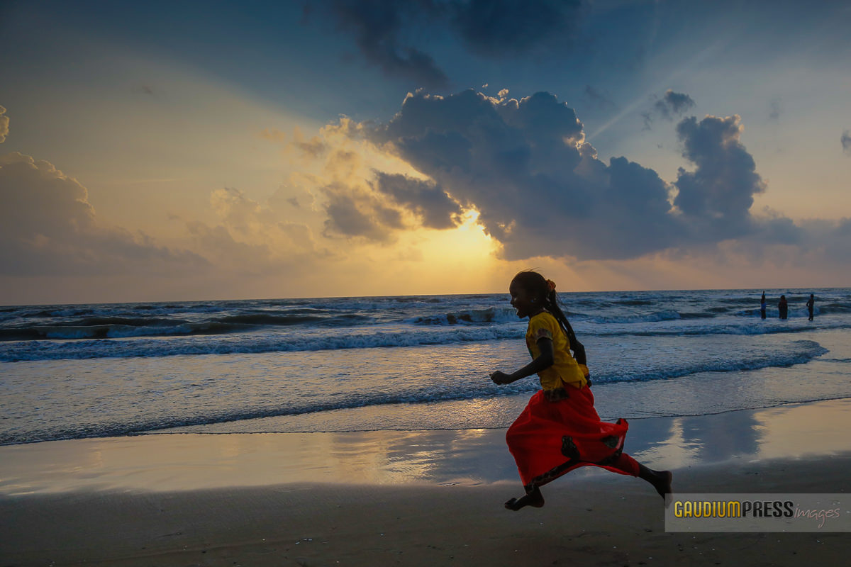 Velankanni, India: a girl runs as sunrise lights the Gulf of Bengal in Tamil Nadu. © Gustavo Kralj/GaudiumpressImages.com